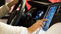 Eine Person, die in einem Auto sitzt und das Navi über das Touch-Display bedient.