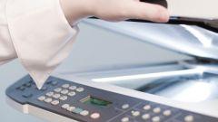 A woman operates a printer.