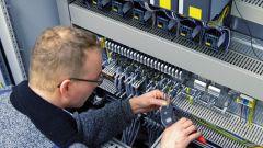 Ein Mann arbeitet an einem Schaltschrank.