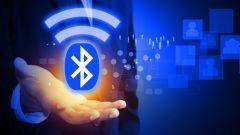 Eine Hand hält ein abstraktes, digitales Bluetooth-Symbol.