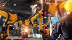 Dieses Bild zeigt einen Ingenieur, der automatische Roboterarme in einer intelligenten Fabrik überprüft.