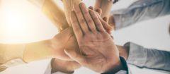 Dieses Bild zeigt Zusammenhalt bei der Arbeit, Mitarbeiter legen ihre Hände übereinander.