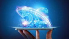Männliche Hand hält ein Smartphone mit einem 5G-Hologramm auf dem Hintergrund einer Stadt.