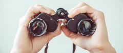 Male hands holding binoculars.